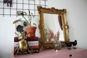 Den coola guldbaggen har Fanny köpt på jobbet. Framför den maffiga guldspegeln står en glasvas med torkad astilbe.
