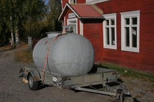 Värdshuset Gästis får vatten via en brandslang, boende i de båda husen på andra sidan vägen får hämta vatten i dunkar från den här tanken.