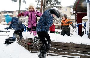 Hopp i snön. Hugo, 3 år, Tuva, 5, Isack, 5 och Li 4 hoppar från lekplatsskeppet.