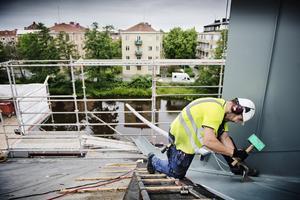 Martin Öberg lägger konserthusets nya tak. Till höger skymtar höjningen av konsertsalens tak.
