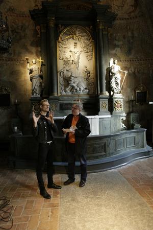 Ljusdesignern Ola Carlsson Fredén och kyrkoherde Ulf Forsberg framför altaret i Edebo kyrka som på lördag inviger sin nya ljussättning.