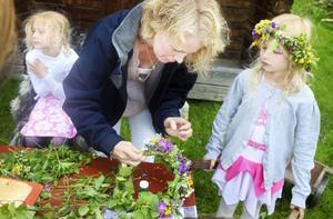 Sofia Waldefors, Elin och Emmy Tronset binder kransar. De får springa iväg och plocka mer blommor, det går åt många när kransen ska bli riktigt fin.