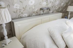 Sänggaveln har paret gjort själva av en garderobsdörr. Bakom finns smart och diskret förvaring.