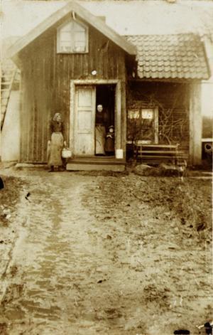 Stugan på Högby skogsfjäll. I det här torpet bodde skomakarmästare Andersson. Till vänster står skomakarens dotter Alice Andersson som var född 1882. Kvinnan och pojken i dörröppningen vet vi inte namnen på. Bilden togs i slutet av 1800-talet.