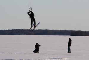 Även om man som åskådarfotograf inte får de bästa ljusförhållandena kan situationen med den duktige drakflygaren på skidor, fotografen och åskådaren bli en bra bild