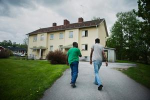 Daoud Soleeman och Taabir Ahmed går upp mot Taabirs hem. Ett bostadshus som inleder med trasig ruta i dörren.