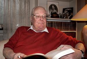 Bertil Öster i Arbrå bläddrar i sin bok.