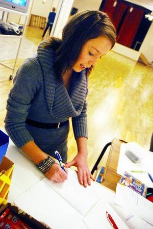 Besökarna på fritidsgården i Rätan får skriva upp sig på en närvarolista. Här är det Sanna Olsén som signerar listan.