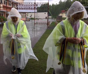 Medaljkullorna avviker från målgång efter en lång stund i hällande regn och tar skydd under frukttältet.