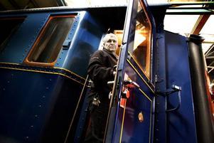 """Kunglig lokförare. Med sina 23,5 meter är kungavagnen för lång för att få plats i Järnvägsmuseets utställningslokaler. I stället får det förvaras i magasinet på Nynäs. """"Vi önskar att vi kunde få lokaler där vi kunde visa upp det"""", säger Sten Holm som kommer att köra ett av de två lok som ska dra vagnen på torsdag."""