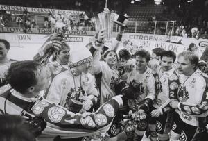 """Anders """"Masken"""" Carlsson lyfter SM-bucklan, omringad av (från vänster) Anders Eldebrink (halverad), Thom Eklund (nummer 4), Niclas Lindgren, Leif R Carlsson (i mössa), Glenn Johansson, Bo Ericson och Peter Ekroth."""