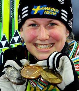 Helena Jonsson visar upp sina tre medaljer från årets skidskytte-VM.