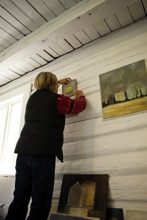 Barbro Bäck hänger upp en av sina akrylmålningar. I dag kan du även se hennes akvareller i Ateljé Blåtorp.