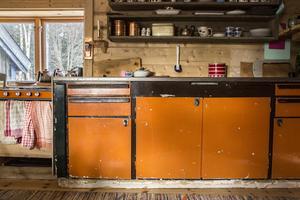 Köksbänken och spisen matchar varandra med sin orangea färg.