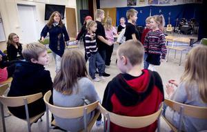 Kerstin Samnell och Jessica Ahlman, vid pianot, leder tredjeklassarna på Lunds skola i Forsa genom musiklektionen.
