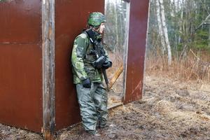 Emil Hjortsberg har precis slängt en handgranat och tar skydd bakom en vägg under övningen i i personlig färdighetsträning.