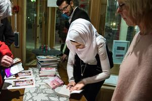 Många vill komma fram och prata när Doaa signerar boken