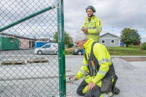 Emil Runsäter och Adrian Johansson från Laxsjö jobbar med att montera upp staket vid Orrvikens skola.