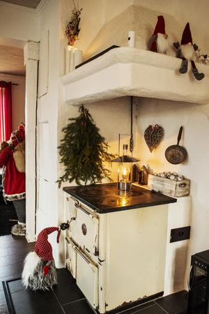 Vedspisen i köket har julpyntats med granris, tomtar och ljus.