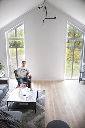 I vardagsrummet är det öppet till nock. Väggen mellan de stora fönstren ut mot trädgården ska snart få ett nytt blickfång – där ska en kamin installeras.