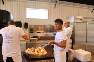 Pizzabagaren Manzulla Sürkhabi visar stolt upp en nygräddad pizza. Till höger står Fredrik Barnelius och till vänster (med ryggen mot kameran)