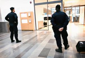 Poliser på post vid tingsrättens entré.