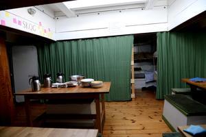 I matrummet var det snart dags att duka och bakom de gröna skynkena fanns det fler sängplatser.