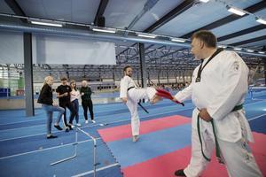 Magnus Svärdström (t.v.), huvudtränare i Gävle taekwondoklubb, visar tjejerna hur de ska sparka.