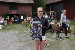 Leah Mörk ska köpa denna ryggsäck på Buskaloppis. Till höger syns Mita Ingstedt och lille Elton.