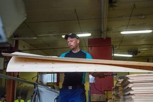 Herman Käck sorterar bort fanér av undermålig kvalitet från produktionslinjen på Plyfa.