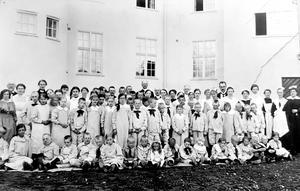 Inför invigningen flyttas 23 barn och unga från Sollefteå till Bodaborg. Här är barn och personal samlade utanför den nya sinnesslöanstalten. Bild: Tillhör Boda Borg