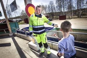 Axel Sandbäck frågar renhållare Göran Wallin vart han ska slänga glasspappret han hittat längst under på släpvagnen.