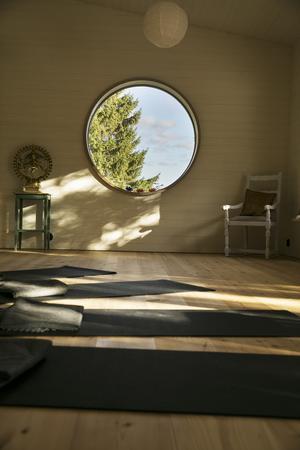 Inne i yogasalen finns ett stort runt fönster som ger ett rofyllt ljus.