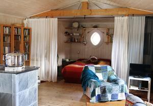 Rummet man kommer in i rymmer sovalkov, soffdel, kontorsdel och en värmande täljstenskamin.