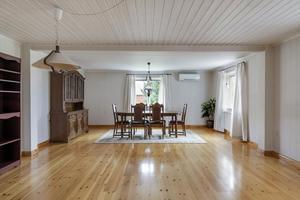 Det rymliga vardagsrummet och matrummet har ett fint trägolv.Foto: Svensk Fastighetsförmedling.