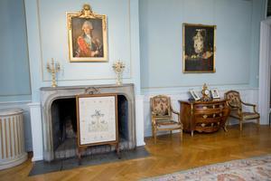Gustav III tronar över spisen i stora salongen.