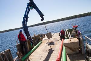 Ett sjömärke, en röd så kallad prick, har slitit sig och med kranens hjälp kan skärgårdsenheten få en ny på plats.