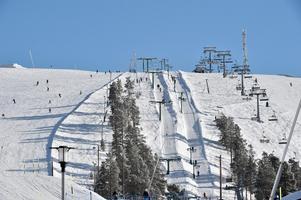 Idre Fjäll i snö och sol med sportlovsgäster.