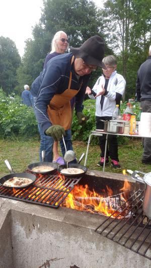 Kvälles kock är Anders Westman som steker kolbullar över öppen eld. I bakgrunden har vi Cecilia Nolander och Birgitta Westman i ett intressant samtal. Foto: Bertil Westin