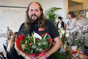 Johan Bjurman, medlem i nya Fontänhuset i Falun, tar emot  blommor från Fontänhuset i Göteborg,