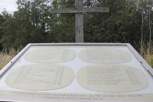 """Här är minnesplatsen för skogskyrkogården på Lillön. Namnen på de som ligger här har graverats in i mässingsplåtar och på det stora korset av ek finns inskriptionen """"De som gick före""""."""