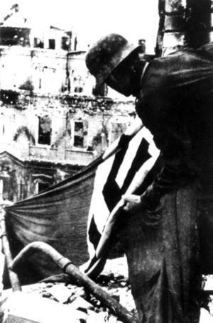 Andra världskriget när 6:e armén kapitulerar i Stalingrad. Soldaten plockar upp en flagga med ett hakkors bland ruinerna. Bild: TT