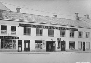 Rosenbergs skrädderi på Storgatan 13. Ägaren Sigfrid (Sigge) Rosenberg står i porten.  Sigfrid Rosenberg började verksamheten 1906 på Järntorget. Okänd fotograf. Bildkälla: Örebro stadsarkiv