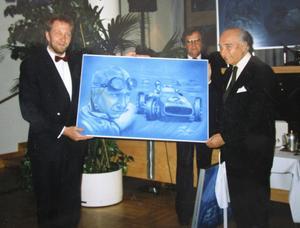Simo Riikonen överräcker en tavla till till racerbilslegenden Juan Manuel Fangio.