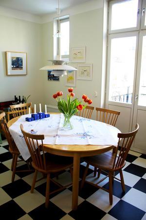 Köksbordet är precis som soffbordet i vardagsrummet gjort i masurbjörk och designat av Hans Ehrlin. Stolarna är Carl Malmstens Lilla Åland. Ovanför bordet hänger en gammal PH-lampa.De blå ljusstakarna på bordet är gjorda av en kollega till Lotta, Västeråskonstnären Stefan Edqvist.