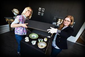 Linda Nordlander Frisk och Elin Timmerholm lyfter på locket som skyddar delar av utställningen.