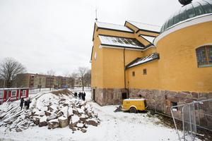 Mängder med jord och sten schaktas bort från   utrymmet under kyrkan.