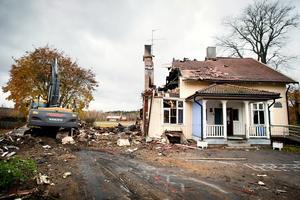Den tidigare lärarbostaden, byggd i början av 1900-talet, rivs nu snabbt via inhyrd grävmaskin. En inhyrd lastbil samt fyra kommunlastbilar forslar brandresterna till Björnhyttans avfallsanläggning.