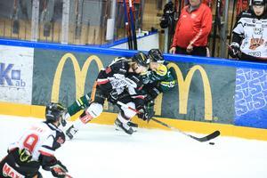 Erik Flood och Erik Rainersson fightas om pucken längs sargen.