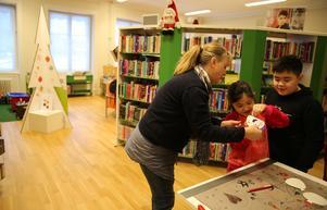 Monica Granlund, biblioteksassistent hjälper några barn med julpyssel.
